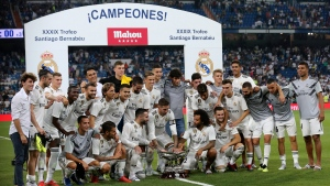 In this Saturday, Aug. 11, 2018 file photo, Real Madrid players pose with the trophy after winning the Santiago Bernabeu trophy soccer match between Real Madrid and AC Milan at the Santiago Bernabeu stadium, in Madrid. Real Madrid's rebuilding process after the departures of Cristiano Ronaldo and Zinedine Zidane gets its first test against crosstown rival Atletico Madrid in the UEFA Super Cup in Estonia on Wednesday, Aug. 15, 2018. (AP Photo/Andrea Comas, File)