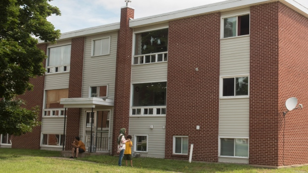 A Family Sits Outside Of An Apartment Building Complex On Brookside Drive Where Four Peopled Including Two Police Officers In A Shooting Last Friday