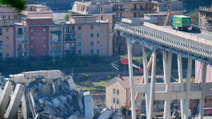 A truck is blocked at the end of the collapsed Morandi highway bridge in Genoa, northern Italy, Wednesday, Aug. 15, 2018. A bridge on a main highway linking Italy with France collapsed in the Italian port city of Genoa during a sudden, violent storm, sending vehicles plunging 90 meters (nearly 300 feet) into a heap of rubble below. (Luca Zennaro/ANSA via AP)