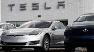 In this July 8, 2018, photo, 2018 Model 3 sedan sits next to a Model X on display outside a Tesla showroom in Littleton, Colo. Board members at Tesla are evaluating CEO and Chairman Elon Musk' $72 billion proposal to take the electric car and solar panel maker private. Six of nine members say in a statement Wednesday, Aug. 8, that Musk began talking with the board about the move last week. (AP Photo/David Zalubowski)