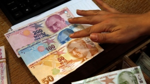 FILE- In this Wednesday, Aug. 15, 2018, file photo a worker at a currency exchange shop exhibits Turkish lira banknotes bearing pictures of modern Turkey's founder Mustafa Kemal Ataturk, in Istanbul. (AP Photo/Lefteris Pitarakis, File)