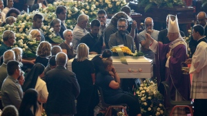 Cardinal Angelo Bagnasco blesses the coffin of nine-year-old Samuel Robbiano during a funeral service for some of the victims of a collapsed highway bridge, in Genoa's exhibition center Fiera di Genova, Italy, Saturday, Aug. 18, 2018. Saturday has been declared a national day of mourning in Italy and includes a state funeral at the industrial port city's fair grounds for those who plunged to their deaths as the 45-meter (150-foot) tall Morandi Bridge gave way Tuesday. (AP Photo/Gregorio Borgia)