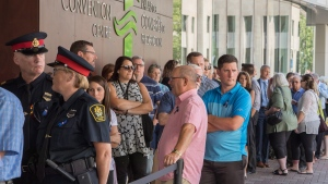 Mourners line up to enter the Fredericton Convention Centre, where a public visitation for Fredericton police constables Sara Burns and Robb Costello is being held, in Fredericton on Thursday, Aug. 16, 2018. THE CANADIAN PRESS/Keith Minchin