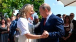 Russian President Vladimir Putin, right, congratulates Austrian Foreign Minister Karin Kneissl as he attends the wedding of Kneissl with Austrian businessman Wolfgang Meilinger in Gamlitz, southern Austria, Saturday, Aug. 18, 2018. (Roland Schlager/pool photo via AP)