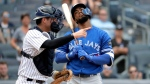 New York Yankees catcher Kyle Higashioka, left, gestures as Toronto Blue Jays' Teoscar Hernandez reacts after striking out looking on a pitch from starting pitcher A.J. Cole to in the ninth inning to end a baseball game, Saturday, Aug. 18, 2018, in New York. (AP Photo/Julio Cortez)