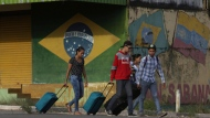 In this March 9, 2018 file photo, young Venezuelans pull their luggage after crossing the border to Pacaraima, Roraima state, Brazil. One of the main border crossings between Brazil and Venezuela has reopened Tuesday, Aug. 7, after a legal fight that kept it shuttered it for nearly a day. It's part of a tug-of-war between a state government overwhelmed by hundreds of Venezuelans arriving every day and the federal government and higher courts, which insist the border must stay open.  (AP Photo/Eraldo Peres, File)