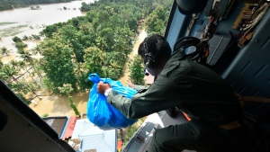 An Indian army soldier airdrops relief material for stranded people at a flooded area in Chengannur in the southern state of Kerala, India, Sunday, Aug.19, 2018. Some 800,000 people have been displaced and over 350 have died in the worst flooding in a century. (AP Photo)