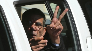 FILE - In this March 30, 2016 file photo, Seif Eddin Mustafa flashes the victory sign from inside a police car after leaving court for a remand hearing in the Cypriot coastal town of Larnaca. Egypt's chief prosecutor says Cyprus extradited Mustafa, the hijacker of an EgyptAir plane that was diverted to the Mediterranean island in 2016. Prosecutor Nabil Sadek said late Saturday, Aug. 18, 2018, that Egyptian police have taken custody of Seif Eddin Mustafa in the Cypriot capital, Nicosia. (AP Photo/Petros Karadjias, File)