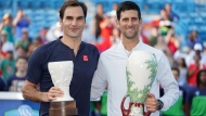 Novak Djokovic, right, of Serbia, holds the Rookwood Cup after defeating Roger Federer, left, of Switzerland, during the finals at the Western & Southern Open tennis tournament, Sunday, Aug. 19, 2018, in Mason, Ohio. (AP Photo/John Minchillo)