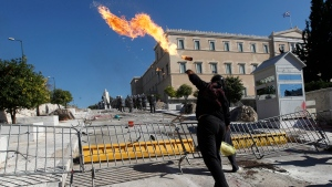 In this Wednesday, Oct. 19, 2011 file photo a protester throws a petrol bomb at riot police during clashes outside the Greek parliament in Athens. Lawmakers approve further tax hikes, further pension and salary cuts, the suspension on reduced pay of 30,000 public servants and the suspension of collective labor contracts, as unions are on a two-day general strike. (AP Photo/Petros Giannakouris, File)