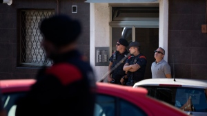 Catalan police officers stand guard at the entrance of a building during a raid, following an attack in Cornella de Llobregat near Barcelona, Spain, Monday, August 20, 2018. Police in Barcelona say they have shot a man who attacked officers with a knife at a police station in the Spanish city. (AP Photo/Emilio Morenatti)