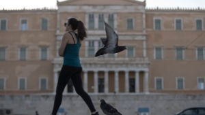 A woman walks past as a pigeon flies in front of Greek Parliament in central Athens, on Tuesday, Aug. 21, 2018. Greece remains shackled to the austerity demands of its former creditors even though it officially entered its post-bailout era Tuesday. (AP Photo/Petros Giannakouris)
