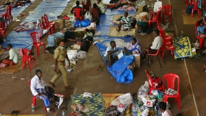 People who have left their flood effected homes take refuge at a relief camp set up at a college on the outskirts of Kochin in the southern state of Kerala, India, Tuesday, Aug. 21, 2018. The Indian military is scaling down rescue operations in the southern state of Kerala, where intense floods killed more than 200 people and drove hundreds of thousands from their homes. (AP Photo/Aijaz Rahi)
