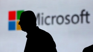 In this Nov. 7, 2017, file photo, a man is silhouetted as he walks in front of Microsoft logo at an event in New Delhi, India. (AP Photo/Altaf Qadri, File)