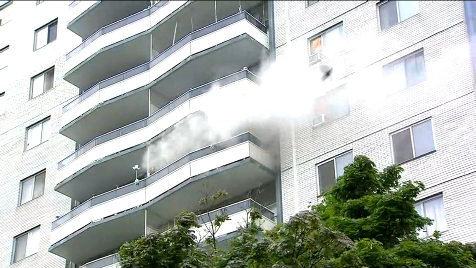 Smoke pours from the balcony of a highrise building on Parliament Street Tuesday August 21, 2018.
