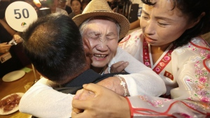 South Korean Lee Keum-seom, 92, center, hugs her North Korean son Ri Sang Chol, 71, left, with Kim Ok Hui, daughter-in-law of Ri Sang Chol during the Separated Family Reunion Meeting at the Diamond Mountain resort in North Korea, Monday, Aug. 20, 2018. Dozens of elderly South Koreans crossed the heavily fortified border into North Korea on Monday for heart-wrenching meetings with relatives most haven't seen since they were separated by the turmoil of the Korean War. (Lee Ji-eun/Yonhap via AP)
