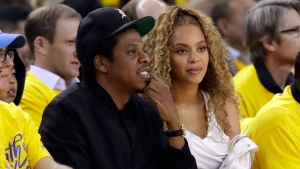 In this April 28 2018, file photo Jay-Z and Beyonce watch Game 1 of an NBA basketball second-round playoff series between the Golden State Warriors and the New Orleans Pelicans in Oakland, Calif. (AP Photo/Marcio Jose Sanchez, File)
