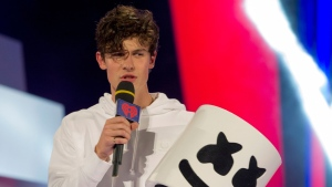 Shawn Mendes arrives on stage with Marshmello's mask at the iHeartRadio MMVAs in Toronto on Sunday, Aug. 26, 2018. THE CANADIAN PRESS/Christopher Katsarov