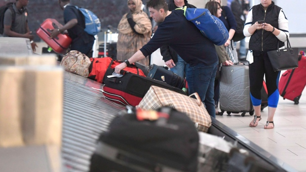Travellers pick up their luggage at a baggage carousel at the Ottawa Airport on Tuesday, May 16, 2017. THE CANADIAN PRESS/Justin Tang