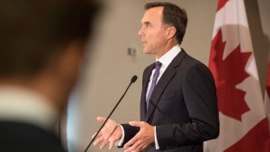 An aide looks on as Federal Finance Minister Bill Morneau addresses journalists in Toronto on Thursday August 30, 2018, as he talks about the government's Trans Mountain pipeline plan. THE CANADIAN PRESS/Chris Young