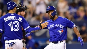 Toronto Blue Jays Teoscar Hernandez is congratulated by teammate Lourdes Gurriel Jr. (13) after hitting a three-run home run during eighth inning baseball action against the Cleveland Indians in Toronto, Sunday, Sept. 9, 2018. (Frank Gunn/The Canadian Press via AP)
