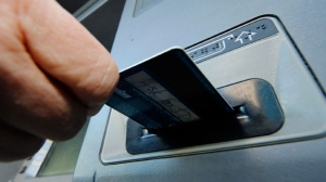 In this Saturday, Jan. 5, 2013 photo, a person demonstrates using a credit card in an ATM machine in Pittsburgh. (AP Photo/Gene J. Puskar)