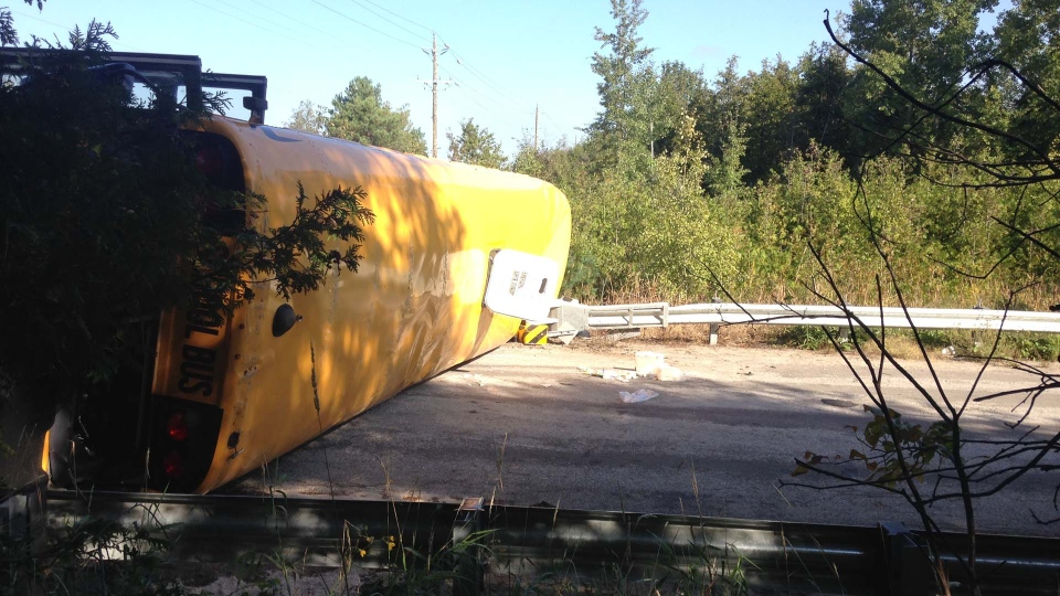 A school bus lies on its side following a collision with a pickup truck at the intersection of 4th line and Sideroad 5 in Innisfil, Wednesday, Sept. 12, 2018. (Krista Sharpe)