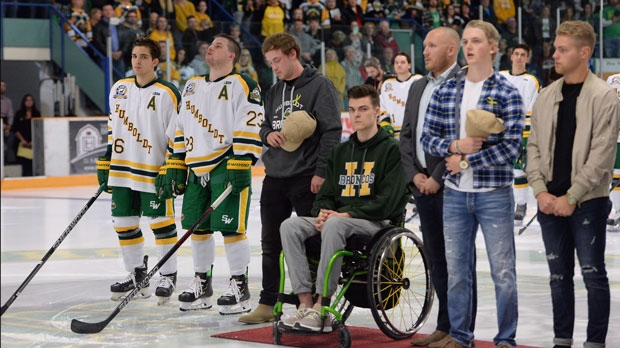 Returning Humboldt Broncos players Brayden Camrud (26) and Derek Patter (23), far left, along with former other teammates stand for the playing of the National Anthem during a pregame ceremony before playing the Nipawin Hawks in the SJHL season home opener Wednesday, Sept. 12, 2018. The Humboldt Broncos are playing their first game since a bus crash claimed 16 lives in April. THE CANADIAN PRESS/Jonathan Hayward