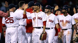 Boston Red Sox right fielder Mookie Betts, center, celebrates with teammates after defeating the Toronto Blue Jays 1-0 for the team's 100th win of the season after a baseball game at Fenway Park in Boston, Wednesday, Sept. 12, 2018. (AP Photo/Charles Krupa)
