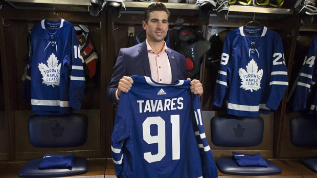 John Tavares holds up a jersey bearing his name in the Maple Leafs' locker room following a news conference in Toronto after signing with the Toronto Maple Leafs on Sunday July 1, 2018. The Maple Leafs are viewed as Stanley Cup favourites after a summer that saw the club add star centre John Tavares in free agency. But as the team gathered for testing and medicals on the first day of training camp, players and management aren't listening to the outside noise. THE CANADIAN PRESS/Chris Young