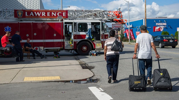 People walk with suitcases and belongings down South Broadway Street in South Lawrence, Mass., Friday, Sept. 14, 2018, after a massive natural gas disaster Friday that affected areas in Lawrence, Andover and North Andover, Mass. (Amanda Sabga/The Eagle-Tribune via AP)