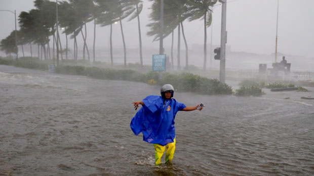 In this Saturday, Sept. 15, 2018, file photo, a man directs traffic to avoid a flooded street at the onslaught of Typhoon Mangkhut which barreled into the northeastern Philippines before dawn in Manila, Philippines. (AP Photo/Bullit Marquez, File)