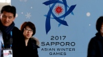 In this Thursday, Feb. 16, 2017 file photo, people walk by a poster for the Sapporo Asian Winter Games, displayed at the main media center in Sapporo on Japan's northern island of Hokkaido. The Japanese city of Sapporo has dropped its bid to host the 2026 Winter Olympics following a recent earthquake. The International Olympic Committee says the city will now focus on a bid for the 2030 Games. (AP Photo/Shuji Kajiyama, File)