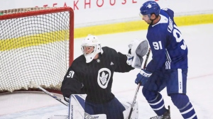 Toronto Maple Leafs forward John Tavares, right, deflects a puck in front of goaltender Frederik Andersen during Maple Leafs training camp in Niagara Falls, Ont., Sunday, September 16, 2018. THE CANADIAN PRESS/Aaron Lynett