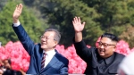South Korean President Moon Jae-in, left, and North Korean leader Kim Jong-un wave from a car during a parade through a street in Pyongyang, North Korea, Tuesday, Sept. 18, 2018. (Pyongyang Press Corps Pool via AP)