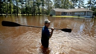 The home of Kenny Babb is surrounded by water as he retrieves a paddle that floated away while the Little River continues to rise in the aftermath of Hurricane Florence in Linden, N.C., Tuesday, Sept. 18, 2018. (AP Photo/David Goldman)