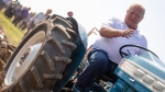 Ontario Premier Doug Ford sits on a Ford tractor as he plows a furrow at the International Plowing Match in Pain Court Ont. Tuesday, September 18, 2018. THE CANADIAN PRESS/ Geoff Robins
