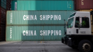 "FILE- In this July, 5, 2018, file photo, a jockey truck passes a stack of 40-foot China Shipping containers at the Port of Savannah in Savannah, Ga. China said Tuesday, Sept. 18, that it will take ""counter-measures"" to U.S. President Donald Trump's decision to raise tariffs on $200 billion of Chinese imports and an American business group warned a ""downward spiral"" in their trade battle appears certain. (AP Photo/Stephen B. Morton, File)"