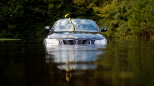 A car sits in a flooded parking lot at an apartment complex near the Cape Fear River as it continues to rise in the aftermath of Hurricane Florence in Fayetteville, N.C., Tuesday, Sept. 18, 2018. (AP Photo/David Goldman)