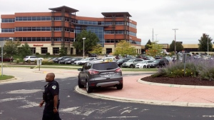 A policer officer walks near the scene where a shooting was reported at a software company in the background in Middleton, Wis., Wednesday, Sept. 19, 2018. Multiple were reported to have been shot. (AP Photo/Todd Richmond)