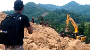 A resident watches as rescuers search for survivors after a landslide struck a village in Naga city, Cebu province central Philippines on Thursday Sept. 20, 2018. A landslide set off by heavy rains buried homes under part of a mountainside in the central Philippines on Thursday, and several people are feared buried, including two who sent text messages seeking help. (AP Photo/Bullit Marquez)