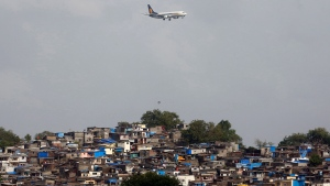 In this June 15, 2016 file photo, an aircraft of India's private airline Jet Airways flies above shanties adjacent to the Chhatrapati Shivaji airport as it prepares to land in Mumbai, India. A Jet Airways flight returned to Mumbai, India's financial capital, on Thursday, Sept. 20, 2018, after dozens of passengers complained of ear pain and nose bleeding due to the loss in cabin pressure. (AP Photo/ Rajanish Kakade, File)