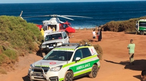 A rescue helicopter and other emergency vehicles are seen at the scene of the shark attack in Gracetown, Australia, Monday, April 16, 2018. A surfer mauled by a shark Monday off southwest Australia managed to swim to shore despite serious injuries to both of his legs, an official and a witness said. (Anthony Pancia/Australian Broadcasting Corp via AP)