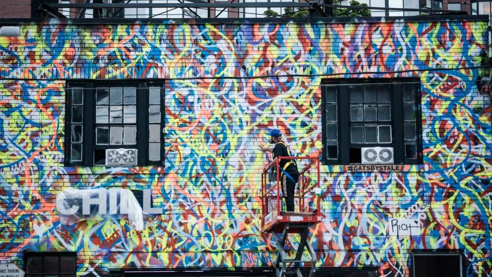 Anthony Ricciardi spray paints the eastern facade of a commercial establishment on Bathurst Street in Toronto, on Monday, July 30, 2018. THE CANADIAN PRESS/Christopher Katsarov