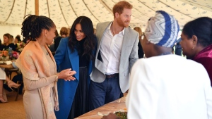 "Meghan, the Duchess of Sussex, centre, talks to her mother Doria Ragland, with Prince Harry at centre right, as they attend a reception for the cookbook ""Together"", at Kensington Palace, in London, Thursday Sept. 20, 2018. The cookbook is being launched with an aim of raising money for victims of the Grenfell fire. (Ben Stansall/Pool Photo via AP)"