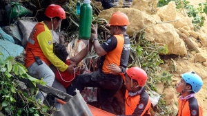 Rescuers pull out a victim from a landslide after it struck their village in Naga city, Cebu province central Philippines on Thursday Sept. 20, 2018. (AP Photo)
