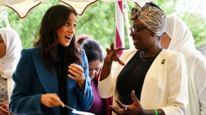"Meghan, the Duchess of Sussex, left, reacts with one of the women behind the cookbook ""Together"" during a reception at Kensington Palace, in London, Thursday Sept. 20, 2018. Markle was joined by her mother for the launch of a cookbook aimed at raising money for victims of the Grenfell fire. The reception was also attended by her mother Doria Ragland and husband Prince Harry. (Ben Stansall/Pool Photo via AP)"