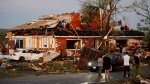 People collect personal effects from damaged homes following a tornado in Dunrobin, Ontario west of Ottawa on Friday, Sept. 21, 2018. A tornado damaged cars in Gatineau, Que., and houses in a community west of Ottawa on Friday afternoon as much of southern Ontario saw severe thunderstorms and high wind gusts, Environment Canada said. (Sean Kilpatrick/The Canadian Press via AP)