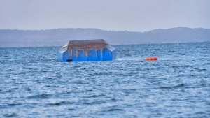 The upturned passenger ferry MV Nyerere floats in the water near Ukara Island in Lake Victoria, Tanzania Friday, Sept. 21, 2018. The death toll rose above 100 after the passenger ferry MV Nyerere capsized on Lake Victoria, Tanzania state radio reported Friday, while a second day of rescue efforts raced the setting sun. (AP Photo)