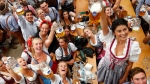 Young women lift glasses of beer during the opening of the 185th 'Oktoberfest' beer festival in Munich, Germany, Saturday, Sept. 22, 2018. The world's largest beer festival will be held from Sept. 22 until Oct. 7, 2018. (AP Photo/Matthias Schrader)